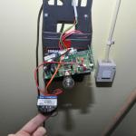 """24V DC hämtas från den svarta plinten, och IN och O1 på brytaren går till plint där """"Extern tryckknapp"""" kan anslutas. Brytaren simulerar därmed en vanlig knapptryckning."""